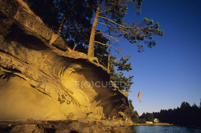 Teenage girl jumping from sandstone ledge, Vancouver Island, British Columbia, Canada. — Stock Photo