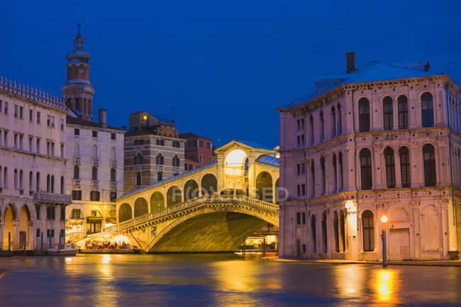 Rialto Bridge and Grand Canal illuminated at night, Venice, Italy — Stock Photo