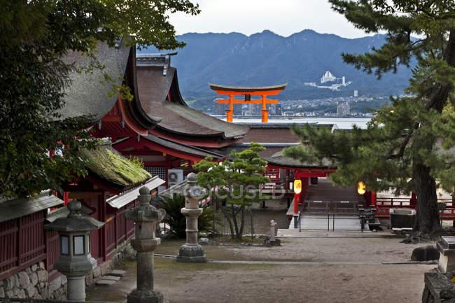 Grounds of Itsukushima Shrine on Miyajima Island with iconic giant torii gate in background, Seto Inland Sea, Japan — Stock Photo