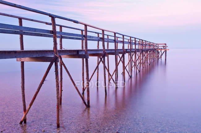 Muelle de madera al atardecer en el lago Winnipeg, Matlock, Manitoba, Canadá . - foto de stock