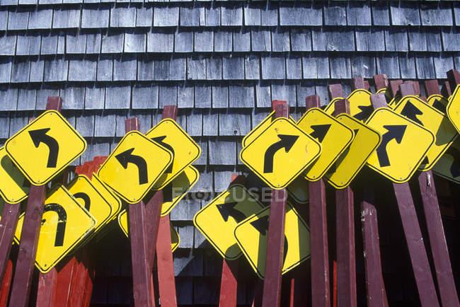 Kurve vor Wegweiser gebündelt zusammen gegen Zedern Holzschindeln Wand — Stockfoto