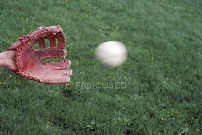 Рука людини з бейсбольною рукавичкою підготовка зловити розмиті бейсбол — стокове фото