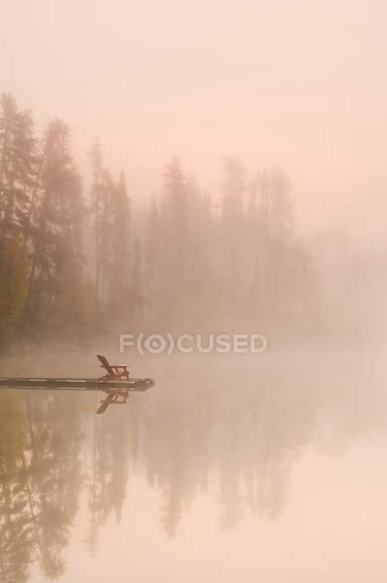 Adirondack chair on wooden dock of Dickens Lake, Saskatchewan, Canada — Stock Photo