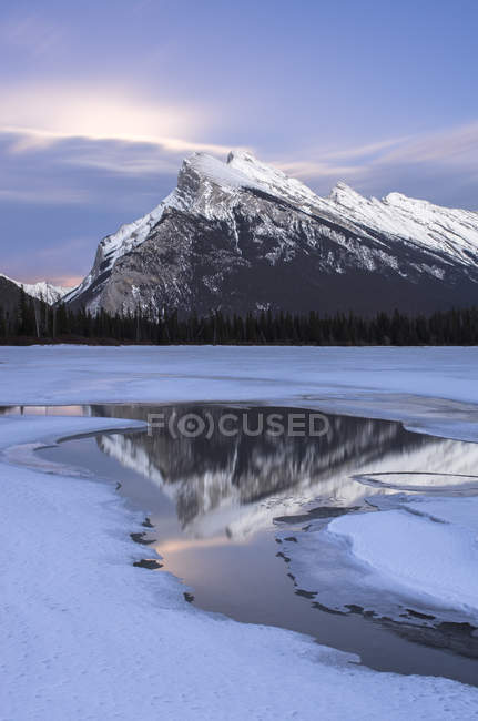 Moonrise behind clouds over Mount Rundle reflecting in Vermilion lake in winter in Banff National Park, Alberta, Canada. — Stock Photo