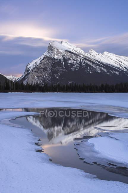 Nascer da lua atrás das nuvens sobre Monte Rundle refletindo no lago vermelhão no inverno no Parque Nacional de Banff, Alberta, Canadá. — Fotografia de Stock
