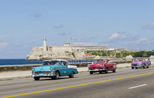 Vintage american cars riding along Malecon with picturesque view of Morro Castle fortress, Havana bay, Havana, Cuba — Stock Photo