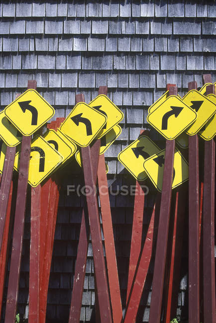 Yellow road signs with arrows stacked near wall — Stock Photo