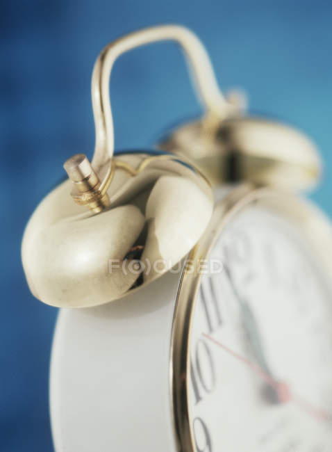 Close up of golden alarm clock on blue background — Stock Photo
