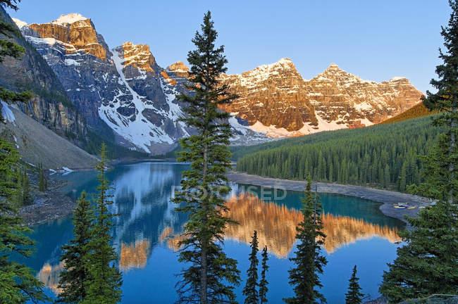 Montanhas, refletindo na água do Lago Moraine no amanhecer, vale dos dez picos, Parque Nacional de Banff, Alberta, Canadá — Fotografia de Stock