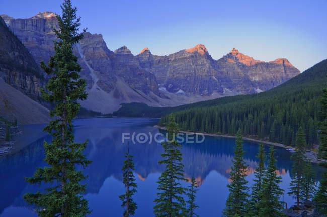 Vista panorámica del amanecer en el lago Moraine en el bosque del Parque Nacional Banff, Alberta, Canadá - foto de stock