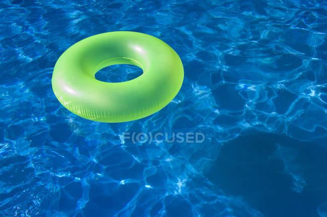 Brinquedo verde anel de flutuação na água azul piscina — Fotografia de Stock