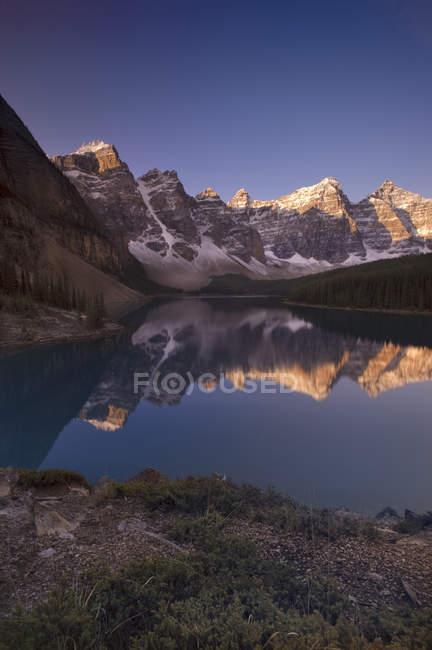 Alpenglow em montanhas rochosas com reflexo no Lago Moraine, vale dos dez picos, Parque Nacional de Banff, Alberta, Canadá. — Fotografia de Stock