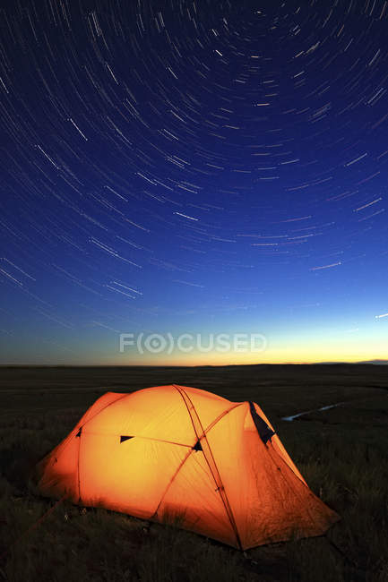 Палатка, загорелась ночью, с видом на долину реки француз, лугопастбищные угодья национального парка, Саскачеван, Канада — стоковое фото