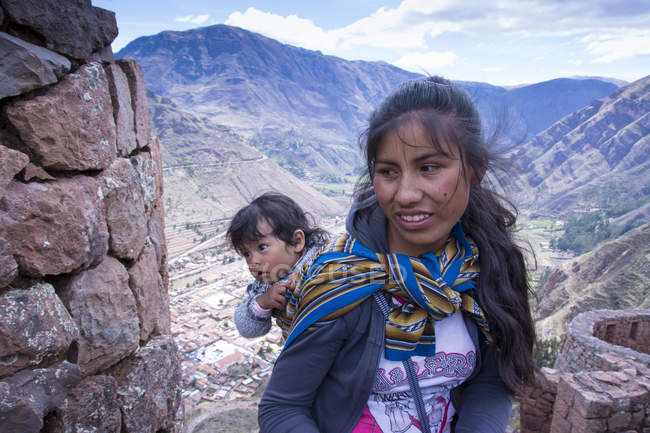 Local woman with daughter in traditional clothing on street of village Pisac, Peru — Stock Photo