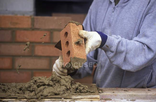Construction site and bricklayer applying mortar while constructing brick wall, British Columbia, Canada. — Stock Photo