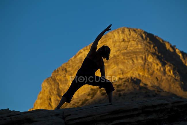 Силуэт женщины йогой на поездку в красной скалы каньона, Лас-Вегас, штат Невада, Соединенные Штаты Америки — стоковое фото