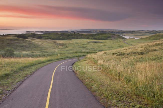 Estrada rural através de prados de Glenbow Ranch Provincial Park, Alberta, Canadá — Fotografia de Stock
