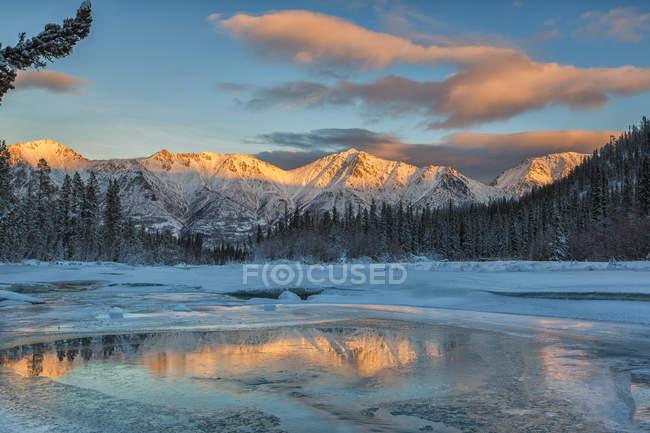 Luz do sol no cume de Gray e nuvens refletindo em Wheaton River para Bennett Lake, Yukon. — Fotografia de Stock