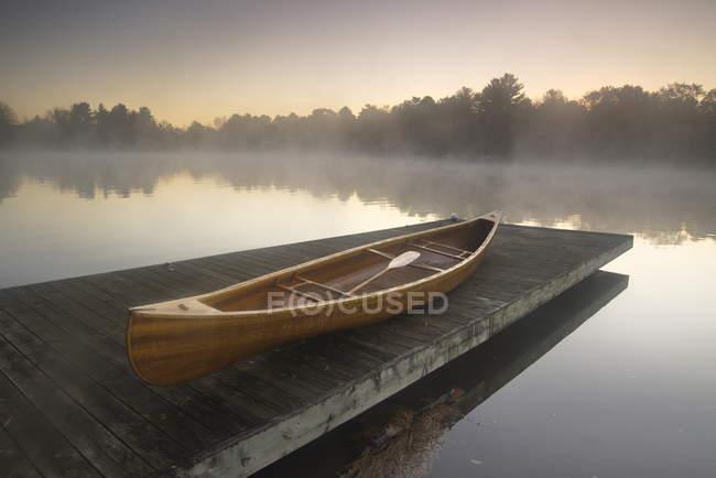 Canoa de madeira amarrada no cais no lago Muskoka em Ontário, Canadá — Fotografia de Stock