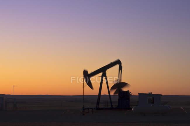 Silhouette of pumpjack near Drumheller at dusk, Alberta — Stock Photo