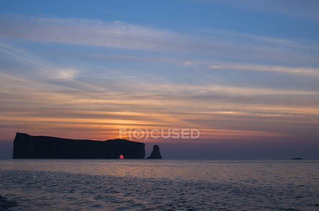 Sun rising behind Perce Rock in Gaspesie, Quebec, Canada. — Stock Photo