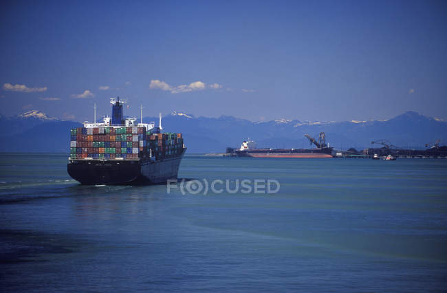 Cargo ships with Coast Mountains beyond, Tsawwassen, Vancouver, British Columbia, Canada. — Stock Photo