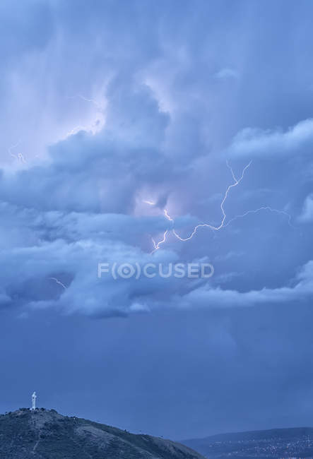 Storm clouds with lightning illuminating El Cristo statue in Cochabamba, Bolivia. — Stock Photo