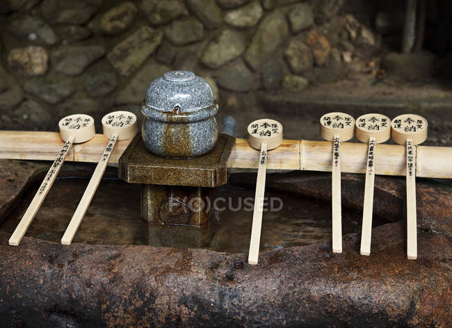Wooden spoons and purification fountain of pure water in Fushimi Inari Shrine, Kyoto, Japan — Stock Photo