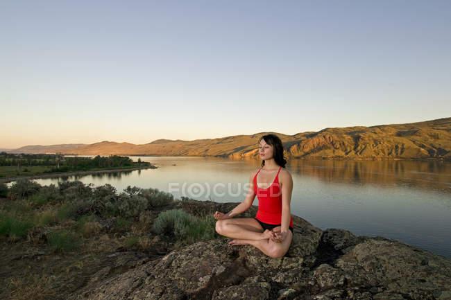 Молодая женщина отдыхает с йогой над озером Камлупс в прекрасный вечер, Камлупс, Британская Колумбия, Канада — стоковое фото