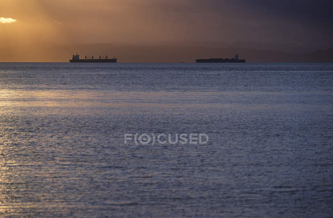 Freighters on water in Georgia Strait at sunset, British Columbia, Canada. — Stock Photo
