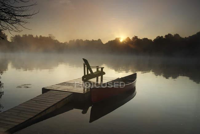 Восход солнца над Каноэ, связаны с док-с Председателем в Мускока, Онтарио, Канада — стоковое фото