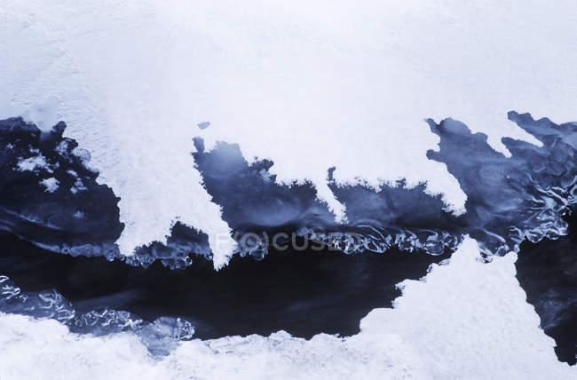 Montagne rocciose che formano ghiaccio e neve sull'acqua a Creek, Columbia Britannica, Canada . — Foto stock