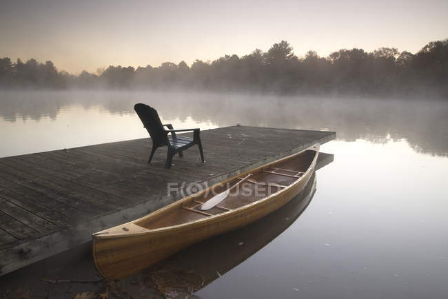 Moored wooden canoe at pier with patio chair on Muskoka lake in Ontario, Canada — Stock Photo