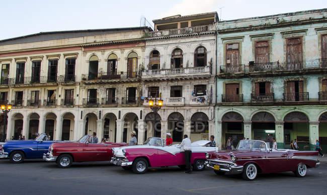Carros americanos clássicos exibindo pela fachada do edifício velho de Havana, Cuba — Fotografia de Stock