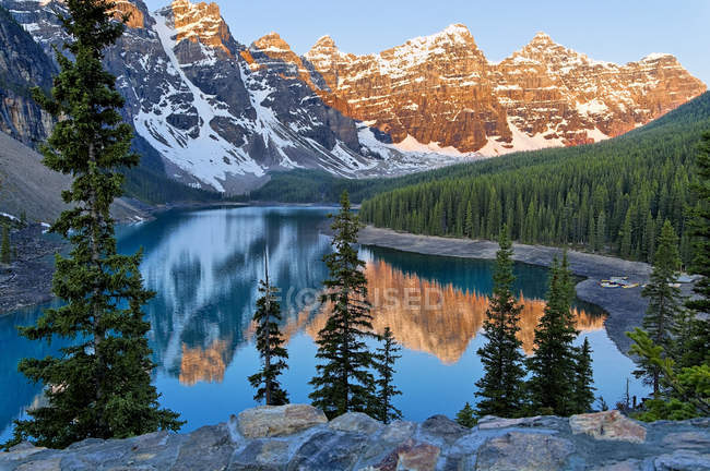 Mountains reflecting in water of Moraine Lake at dawn, Valley of Ten Peaks, Banff National Park, Alberta, Canada — Stock Photo