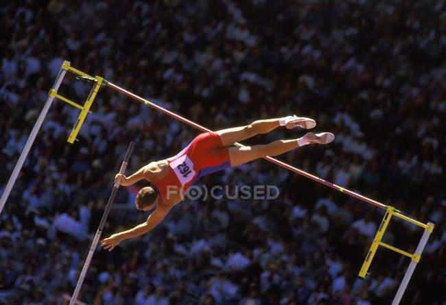 Мужской прыгун с шестом распространяется на полный прыжок, Британская Колумбия, Канада. — стоковое фото