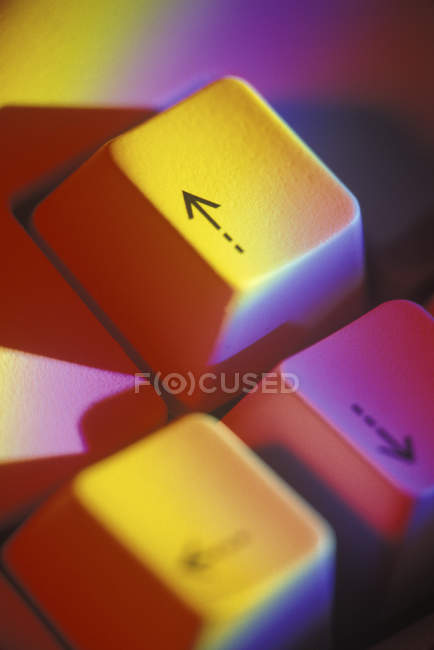 Keyboard buttons with arrows in yellow light — Stock Photo