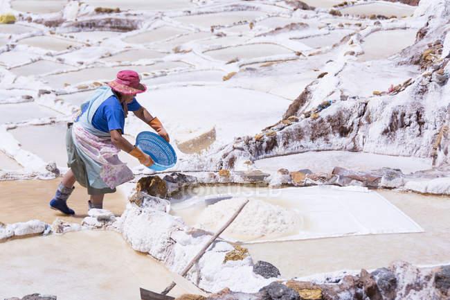 Einheimische, die in den Salzbergwerken von Maras in der Region Cuzco in Peru arbeitet — Stockfoto