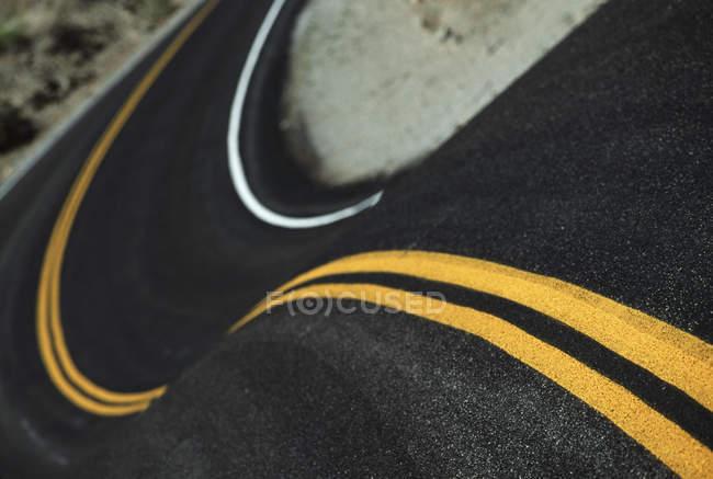 Primo piano sulla tortuosa strada con linee gialle — Foto stock