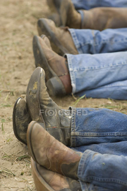 Bottes et jeans de Cow-Boys prenant la pause au printemps branding, Saskatchewan, Canada. — Photo de stock