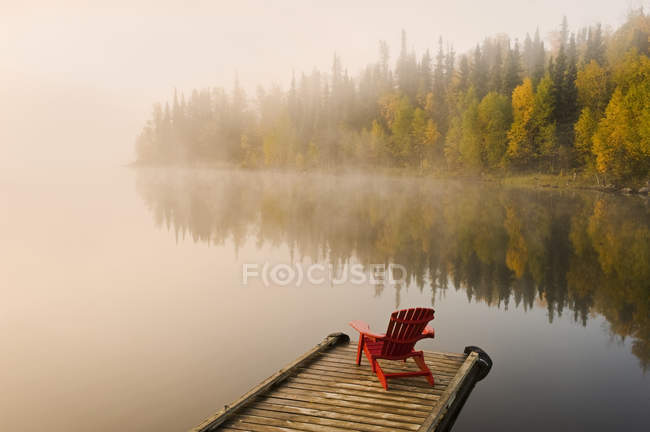 Chaise Adirondack sur quai en bois du lac Dickens, Saskatchewan, Canada — Photo de stock
