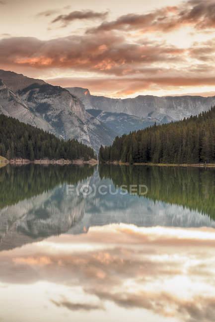 Восход солнца над деревьями, отражая в воде двух Джек озера, Национальный парк Банф, Альберта, Канада — стоковое фото
