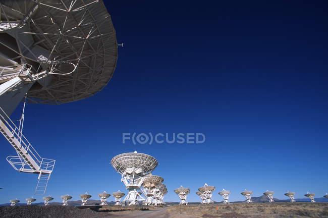 Large gamme de antennes paraboliques contre le ciel bleu au Nouveau-Mexique, États-Unis . — Photo de stock