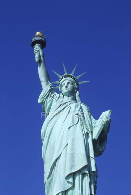 Vista ad angolo basso della Statua della Libertà contro il cielo blu a New York, USA — Foto stock