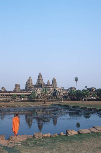 Буддійський чернець, стоячи в передній турботах ставок храм Ангкор-Ват, Siem Reap, Камбоджа — стокове фото