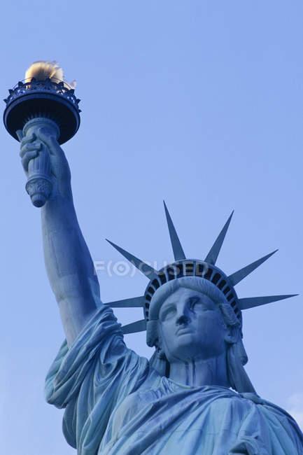 Vista ad angolo basso della testa della Statua della Libertà e dettaglio della torcia contro il cielo blu a New York, USA — Foto stock