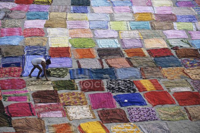 Lavadora sobre telas secas en la arena del río, Agra, Uttar Pradesh, India - foto de stock