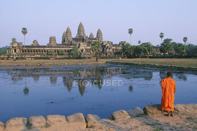 Moine bouddhiste debout devant l'étang reflétant le temple Angkor Wat, Siem Reap, Cambodge — Photo de stock