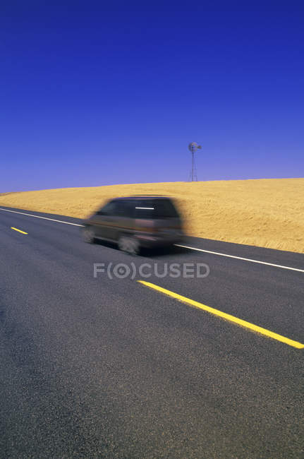 Car moving along wide roadway in golden field in Palouse, Washington State, USA — Stock Photo