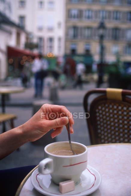Кафе з жіночим ручним перемішуванням кави, Париж, Франція — стокове фото
